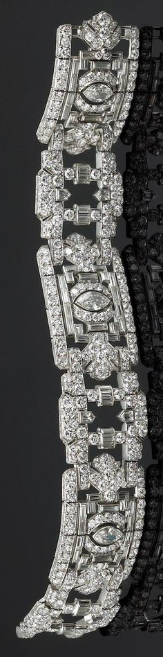 A late Art Deco diamond bracelet of flexible design, the three geometric panels each centring a marquise-cut diamond, surrounded by baguette and round brilliant-cut diamonds within an openwork frame, further enhanced by diamond set links of bullet-shaped diamonds and arched diamond spacers; estimated total diamond weight: 23.10 carats; mounted in platinum. #ArtDeco #braceletdiamonds