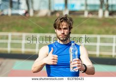 handsome man or guy with muscular body holds plastic refreshing water bottle showing thumb up sunny outdoor in blue sportswear at stadium. fitness and healthy lifestyle concept - Shutterstock Premier