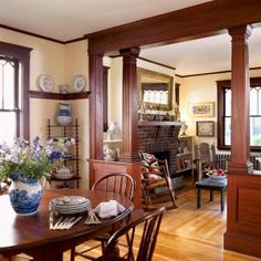 A Sweet & Simple Cottage Bungalow: The fluted square columns of the colonnade frame the corbelled brick fireplace in the 1920s parlor.