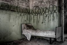 Creepy wall art from an abandoned mental institution in Italy.