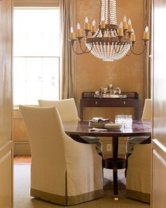 A round mahogany table in the dining room offers an intimate spot for meals. The painted plaster walls have a honey hue, and the silk-and-linen slipcovers give the dining chairs a pared-down profile. The iron-and-crystal chandelier is a Niermann Weeks design.