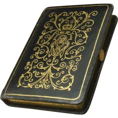 Small navy blue leather bound book which is actually a compact. The compact opens by sliding the tab. Inside is the original mirror, a powder section