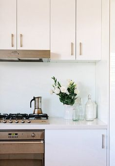 White overhead cupboards, white splashback, white stone bench and white cupboards below.  yes yes yes.
