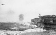 Captured British tank with German markings crossing a trench. Note a biplane flying over the battlefield. 1918.