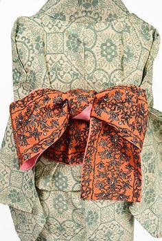 深みのあるオレンジに、シックな黒ときらめくシルバーの色で織りだされた瀟洒に美しいアラベスク模様が形作るボーダーデザインがロマンチックなビンテージの半幅帯です。