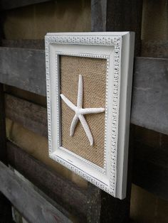 Any frame old or new painted white. Burlap attached to frame back. Star fish attached after burlap. Cheap and simple way to add character.