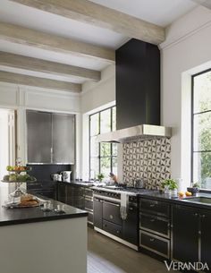 A graphic backsplash energizes this sleek black-and-white kitchen.