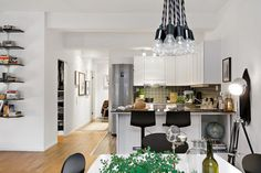 Check Out This Attractive Apartment With Industrial Touches In Central Sweden : Swedish Apartment Dining Room Laminate Floor White Wall Unique Pendant Lamp Tripod Spot Light Black Chair Bar Stool Kitchen Counter Island And Cabinet Refrigerator Black Tile Backsplash