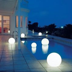Gorgeous outdoor globe lights, could recreate with ikea globes and rechargable LED lights?