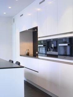 Keuken renovatie met ingebouwde toestellen en hoogglans afwerking. Ingebouwde kastenwand op maat.