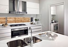This kitchen has a really nice modern design. I love the bamboo backsplash. It is a really nice feature to have in a kitchen.