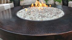 """Oriflamme Round Hammered Copper Firepit   42"""" diameter x 19""""H   150 lbs.   up to 65,000 BTU   30-40 hour burn capacity   I think these ratings are when using two propane tanks.   I don't know if the copper tabletop gets hot. I'm guessing not, but am not certain."""