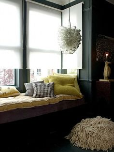 i like the blinds and the dark walls with that green. not so in love with the mop-textured pouf -- though maybe it's a sleeping Puli. that would be rad.