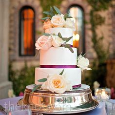 Fresh roses, eucalyptus greens and thin purple ribbon spruced up the three-tiered white cake.