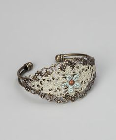 Pairing romantic filigree swirls with a hand-painted vintage design, this fanciful cuff is fit for any style maven who prefers to wish upon a star to make her fashionable dreams come true.