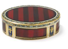 A SWISS ENAMELED GOLD SNUFF BOX, LATE 18TH CENTURY oval, decorated wtih claret translucent enamel on engine-turned striped ground, borders of running leaves, the sides with urns  marked inside base F crowned, other marks not clear  length 2 7/8 in.