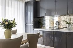 Glamorous kitchen with striking eglomise splashback in chic contemporary London apartment designed by boutique interior design studio, Anouska Tamony Designs.