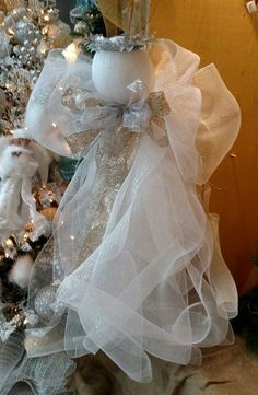 """Deco mesh angel with silver and champagne ribbon and silver halo To make: 1 Xlg styro ball, 2-3 rolls 21"""" white deco mesh, ribbon for bow, wire, glamour rope & silver leaves for halo.  To make wings: gather mesh in a double bowtie type bow (no streamers). I used tinsel wire to tie off, make sure it's a long piece so you can tie around angels neck to secure to angel! To make head & body: Lay out deco (unrolled) I used partial roll first overlap each piece in middle but each piece going diff…"""