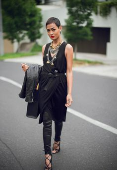 Black outfit: leather jacket and trousers/leggings, statement jewelry and a short pixie cut.