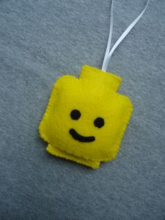 This Lego head felt ornament measures about inches tall and 3 inches wide. This yellow ornament hangs from satin ribbon and is completely handstitched by me. All my products are made in a smoke free, pet free home. Lego Christmas Ornaments, Handmade Christmas, Christmas Crafts, Diy Ornaments, Lego Head, Lego Craft, Lego Birthday, Legos, Christmas