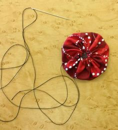 A yo-yo is a circle of fabric that has the edge turned under and secured with a running stitch to make a three-dimensional circle. See how to make one here.