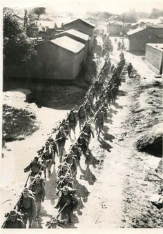 1937- Japanese reinforcements, replacing the original landing parties, marching along a narrow road to take up their positions near Shanghai