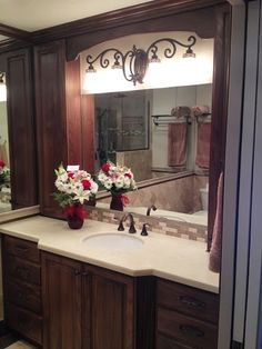 Bathroom Remodel: Dark chocolate brown wood cabinets contrasted with cream colored stone counter top with a bronze faucet and vanity detail