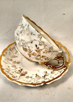 DISCOUNTS>>>>>10% OFF purchase of 2 or more items priced $25 or more each. Porcelain Coffee Cup and Saucer Gold Trim Scallop Rim Gold Floral Motif 1 3/4 high 2 1/2 cup diameter 3 3/4 saucer diameter No chips, No cracks, No crazing Ships Worldwide Free Local Pickup NYC
