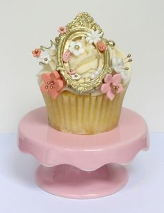 "From the designer, Florence Sabourin-Poirier: ""This lovely cupcake was inspired by my love of classic romantic literature, and would feel at home in the middle of a beautiful English garden. The focal point is obviously the edible golden frame, but it is really a delicate piece with a lot of detail and space, which still lets the neatly chaotic arrangement of flowers shine."""