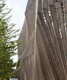 Les Yeux Verts by Jacques Ferrier Architecture. Parking garage with eye-shaped openings, framed with hanging gardens.  This view: undulating timber facade.