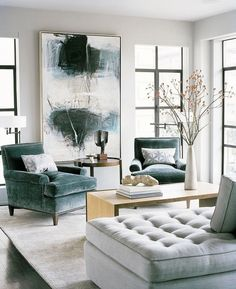 This luxurious living room hits all the right notes with a cool color palette of gray, blue, and white and sumptuous fabrics like velvet and linen. While there is no pink in sight, the décor remains quite feminine. It's beautifully balanced by the industrial windows that line the room, which also serve to anchor the space and make it feel more intimate
