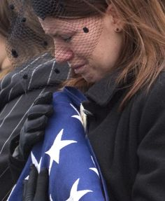 Kait Wyatt clutches a flag during the burial service for her husband, Marine Cpl. Derek Wyatt at Arlington National Cemetery in Arlington, Va., Friday, January 7, 2011. Wyatt, of Akron, Ohio, was killed Dec. 6 in Afghanistan. Wyatt's son was born 24 hours after his wife received the news of his death.