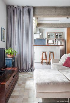 Os espaços da sala e cozinha desse apê foram divididos com o uso de uma cortina.