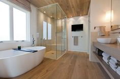 Luminoso bagno moderno con pavimenti e soffito in legno, vasca in acrilico e box doccia in vetro e marmo - Start Preventivi