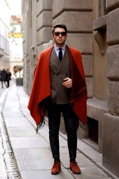 This combination of a red overcoat and black chinos is definitely eye-catching, but it's also extremely easy to assemble. With shoes, you could take a classier route with red suede derby shoes. Style Dandy, Style Gentleman, Mens Poncho, Mens Cape, Light Blue Dress Shirt, Mode Shoes, Herren Style, Look Man, Black Chinos