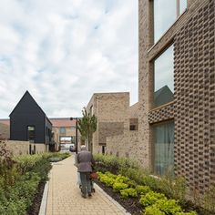 Patterned brickwork reveals the entrances to all the homes in this residential development near Cambridge, England, designed to bring a sense of continuity