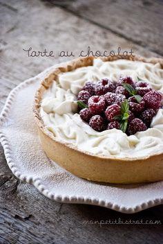 Tarte au chocolate with whipped cream and raspberries