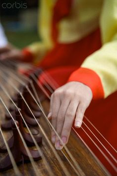 Woman in Hanbok is playing gayageum  (I listened to a musician perform on it in college)