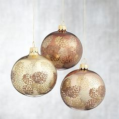 Artful pinecones cluster in warm metallic tones on these beautiful shiny ball ornaments. Each hand-decorated, blown-glass ornament is skillfully crafted by Polish artisans using time-honored techniques.
