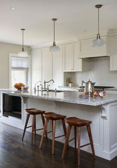 Beautifully appointed kitchen boasts a long white center island fitted with a television mounted beneath a gray quartz countertop finished with a dual stainless steel sink and a polished nickel vintage deck mount faucet kit lit by white glass vintage light pendants.