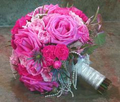 Lolipop bouquet with pearl strands. This bouquet is made with a special water holder to keep the bouquet lasting for days after the wedding. This bouquet has roses, spray roses, garden spray roses, lambs ear, thistle, and rose of sharon.