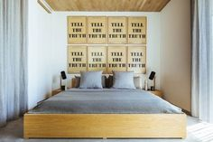 Matching ink-on-paper prints in rustic frames make a graphic statement above the simple wood bed, another Melilla design | archdigest.com