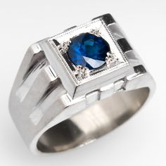 Vintage Geometric Mens Sapphire Ring 14K White Gold -  This handsome gents ring is centered with a 1.35 carat round cut blue sapphire set into a square plaque. The plaque sits atop geometric shoulders and a wide shank. The ring is crafted of solid 14k white gold and is in good condition showing some light wear and a few dings to the gold.