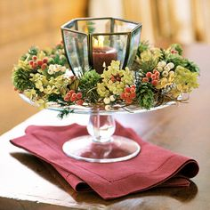For winter, remove the fall flowers, leaving the plain wreath intact. Insert small pieces of evergreens, white winterberries, green hops, red pepper berries, and frosted beads. Replace the candle with a red or white one.
