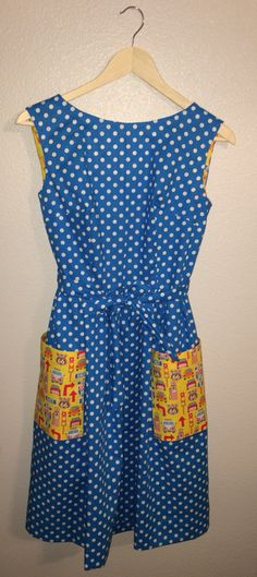 Step in back wrap dress in cyan with white polka dots and yellow VW bus print accent. Tie belt. Hook and eye back closure. Machine blind hem. Pockets reinforced with interfacing. Authentic 1950s pattern. Size 6-8.