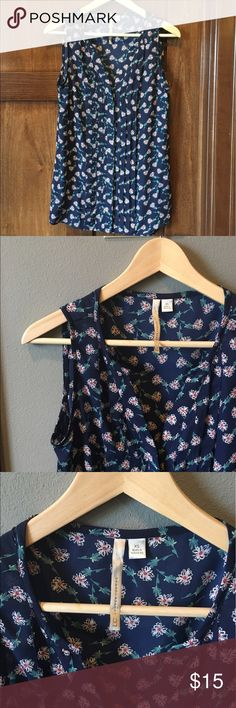 LC Lauren Conrad Floral Sleeveless Blouse Lauren Conrad LC floral sleeveless button down blouse. Light weight material and slightly sheer.  Dark blue background with pink and white flowers.  Flower stems are light blue and green.  The bodice has a pleated type detail covering the buttons.  So cute and perfect for this spring and summer season.  This is an XS but fits more like a small.  Made of 100% polyester.  Offers considered through offer button. LC Lauren Conrad Tops Blouses