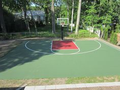 This is a forest green and red concrete backyard basketball court we painted in Short Hills, NJ.
