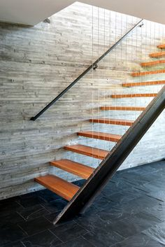 The outdoors dictated the design in other ways. The two-story concrete wall that lines the open riser stairway absorbs heat in the winter and retains cool night air in the summer.