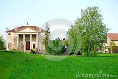 Photo taken to a Palladian villa located along the state road connecting Padua and Vicenza in Veneto (Italy). Picture picked up from the street you see the facade faces south and illuminated by the afternoon sun. In front of the entrance you see the broad and classical portico supported by four tall columns, on the right there are some trees and another building.