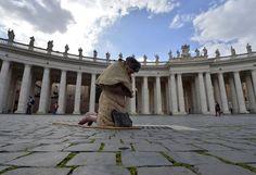 Un homme pieds nus prie sur la place Saint-Pierre, au Vatican, le 12 mars 2013.